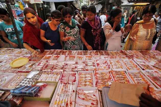 नई दिल्ली में महिलाएं और युवतियां अपने भाइयों के लिए राखी खरीदती हुईं। (तस्वीर: एपी)
