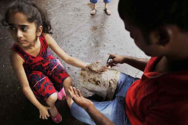 रक्षाबंधन की पूर्व संध्या पर दिल्ली में एक बच्ची मेहंदी लगवाती हुई। (तस्वीर: एपी)
