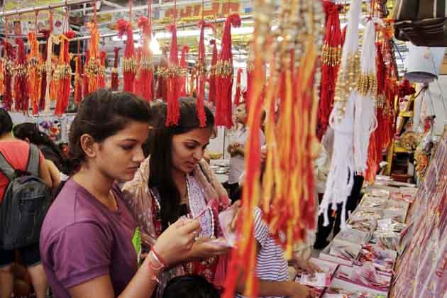 अहमदाबाद में रक्षाबंधन की पूर्व संध्या पर भाई के लिए राखी खरीदती बहनें। (तस्वीर: एपी)