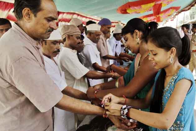 अहमदाबाद के सेंट्रल जेल में बंद अपने भाइयों की कलाइयों पर राखी बांधती बहनें। (तस्वीर: एपी)