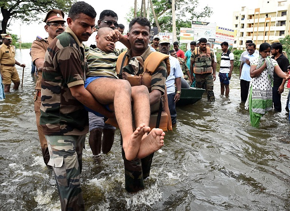 Indian Army personnel rescue flood-affected people during their relief operations in rain-hit areas on the outskirts of Chennai on November 17, 2015. India has deployed the army and air force to rescue flood-hit residents in the southern state of Tamil Nadu, where at least 71 people have died in around a week of torrential rains. AFP PHOTO (Photo credit should read STR/AFP/Getty Images)