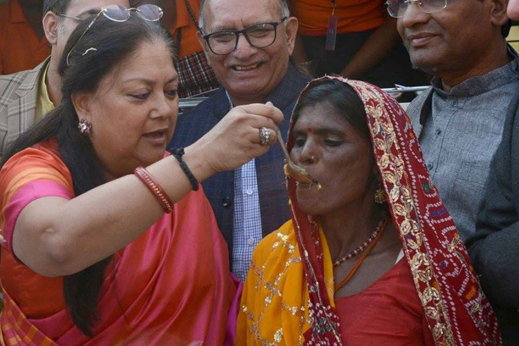 एक महिला को खाना खिलाते हुए सीएम वसुंधरा।