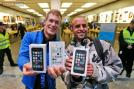 First customers of the Apple store in Oberhausen are all smile with their new iPhones in hand as they leave the store after the start of the new iPhone sale in Oberhausen, Germany, Friday, September 20, 2013. AP Photo/Frank Augstein