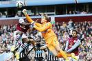 Newcastle United's goalkeeper Tim Krul punches the ball away as he is challenged by Aston Villa's Aly Cissokho during their English Premier League soccer match at Villa Park.