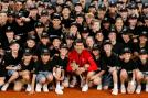 Novak Djokovic holds his trophy while posing with ballboys. (Reuters Photo)