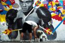 A man places a candle under a mural of the late boxer Muhammad Ali in New York. (Getty Images)