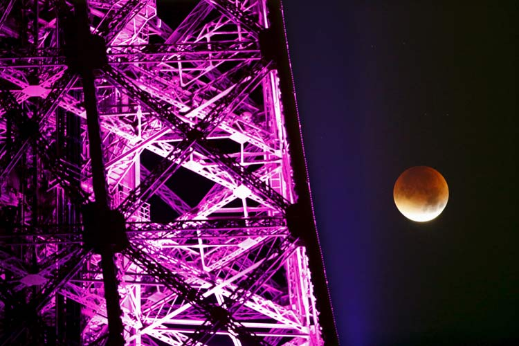 "The Moon, appearing next to the Eiffel Tower in a dim red colour, is covered by the Earth's shadow during a total lunar eclipse over Paris, France September 28, 2015. Sky-watchers around the world were treated when the shadow of Earth cast a reddish glow on the moon, the result of rare combination of an eclipse with the closest full moon of the year. The total ""supermoon"" lunar eclipse, also known as a ""blood moon"" is one that appears bigger and brighter than usual as it reaches the point in its orbit that is closest to Earth. REUTERS/Charles Platiau"