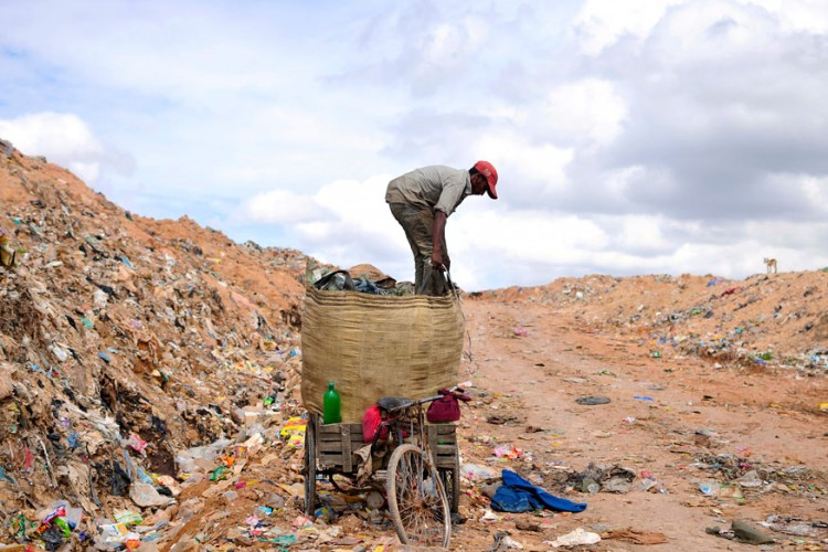 A rag picker prepares to pack a sack filled with recyclable materials at a garbage dump in Bangalore. (Photo: Reuters)