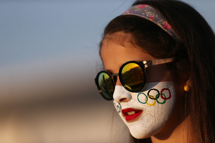 A young girl with her face painted with the Olympic rings smiles as she attends the women's first round singles tennis match. (Photo Credit: Reuters)