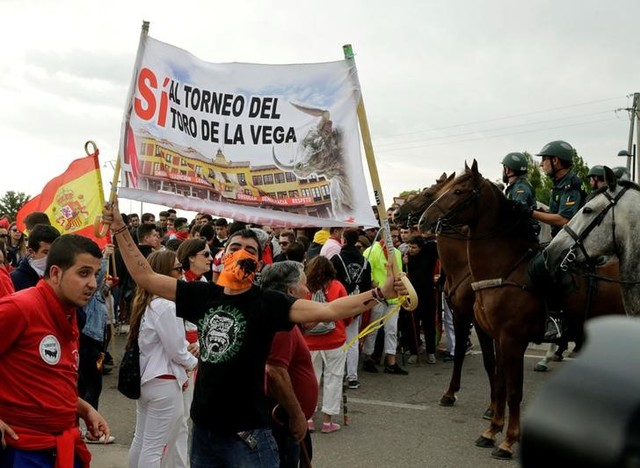 Revellers hold a banner in support of the Toro de la Vega next to Spanish Civil Guard officers before the start of the Toro de la Pena, in Tordesillas, Spain
