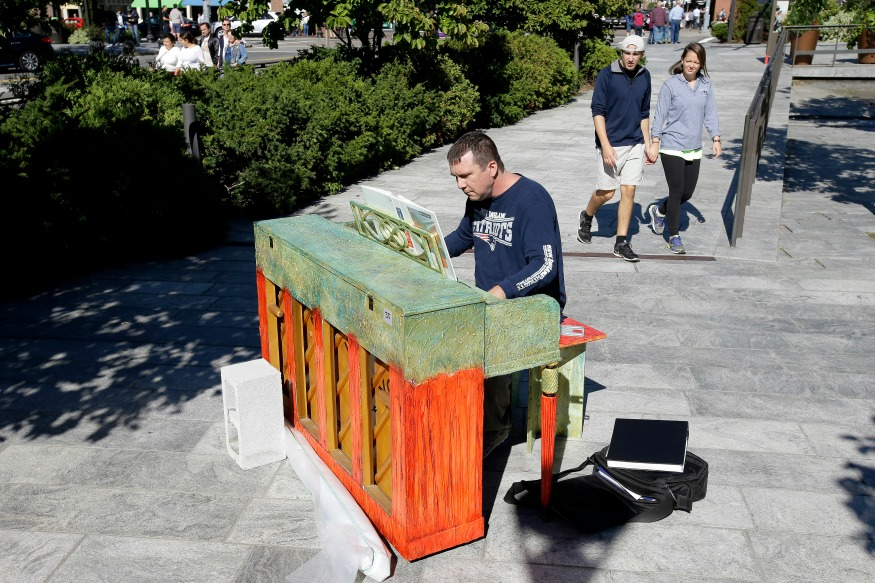 "(Photo: AP/A number of working pianos painted by local artists have been placed around Boston and Cambridge, each with a simple message to passersby: ""Play Me, I'm Yours."")"