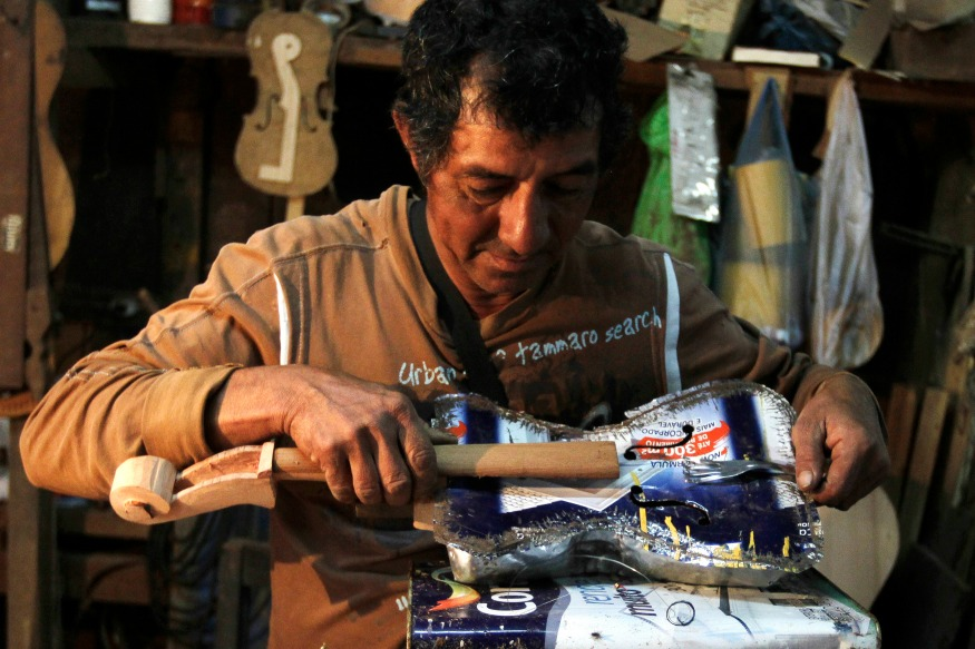 (Photo: Reuters/Trash recycler and craftsman Nicolas Gomez makes a violin from a paint tin and dinner fork for the Orchestra of Recycled Instruments of Cateura.)