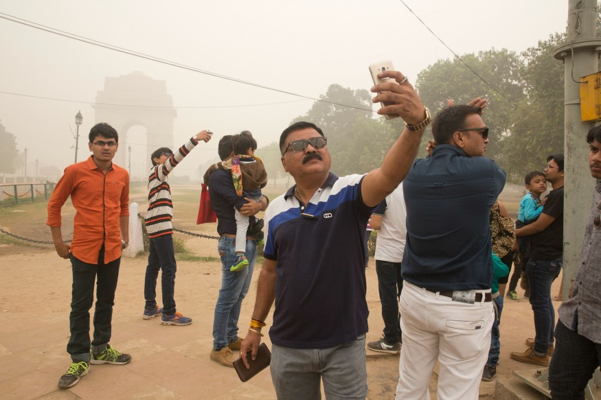 (Photo : AP/ Indian tourists take selfies against India Gate engulfed in smog.)