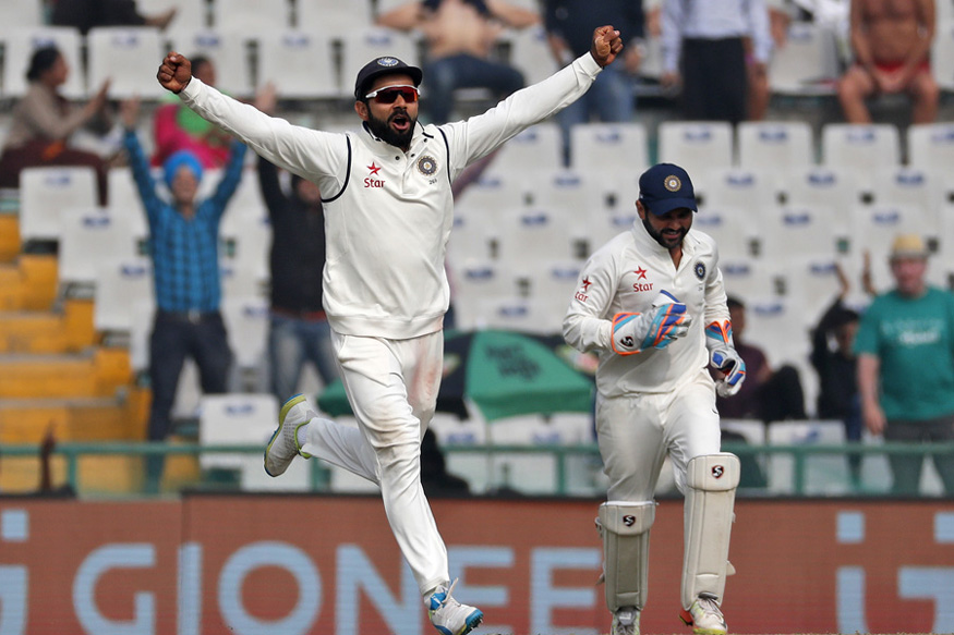 Indian test cricket team captain, Virat Kohli, left, celebrates the dismissal of England's Adil Rashid on the fourth day of their third cricket test match in Mohali, India. (AP Photo)