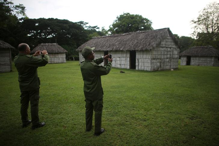 Army officers take photographs with their mobile phones during a guided visit to the estate where Cuba's former President Fidel Castro and his brother Raul were born in Biran