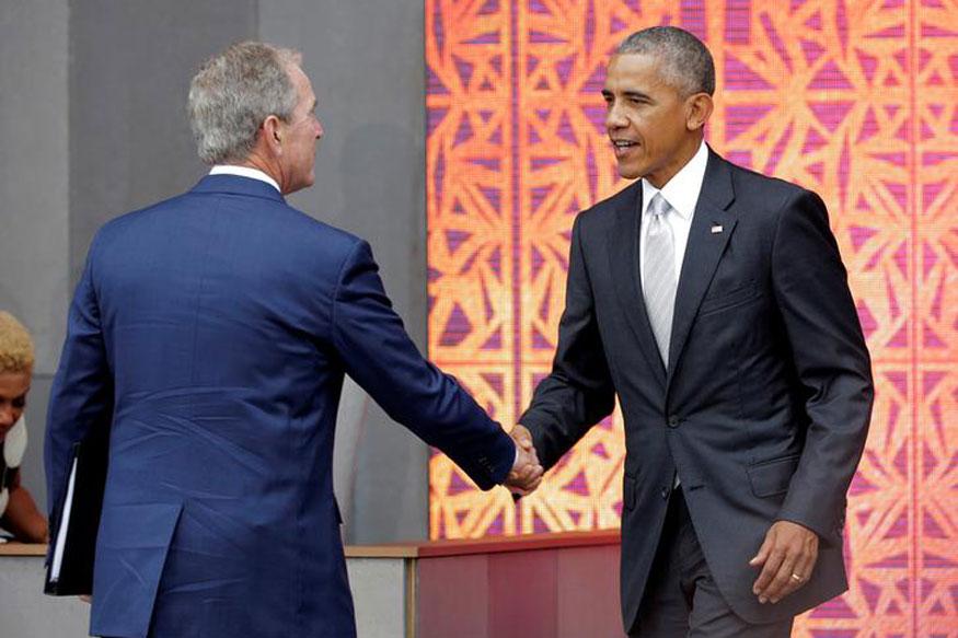 U.S. President Barack Obama shakes hands with former U.S. President George W. Bush (Reuters)