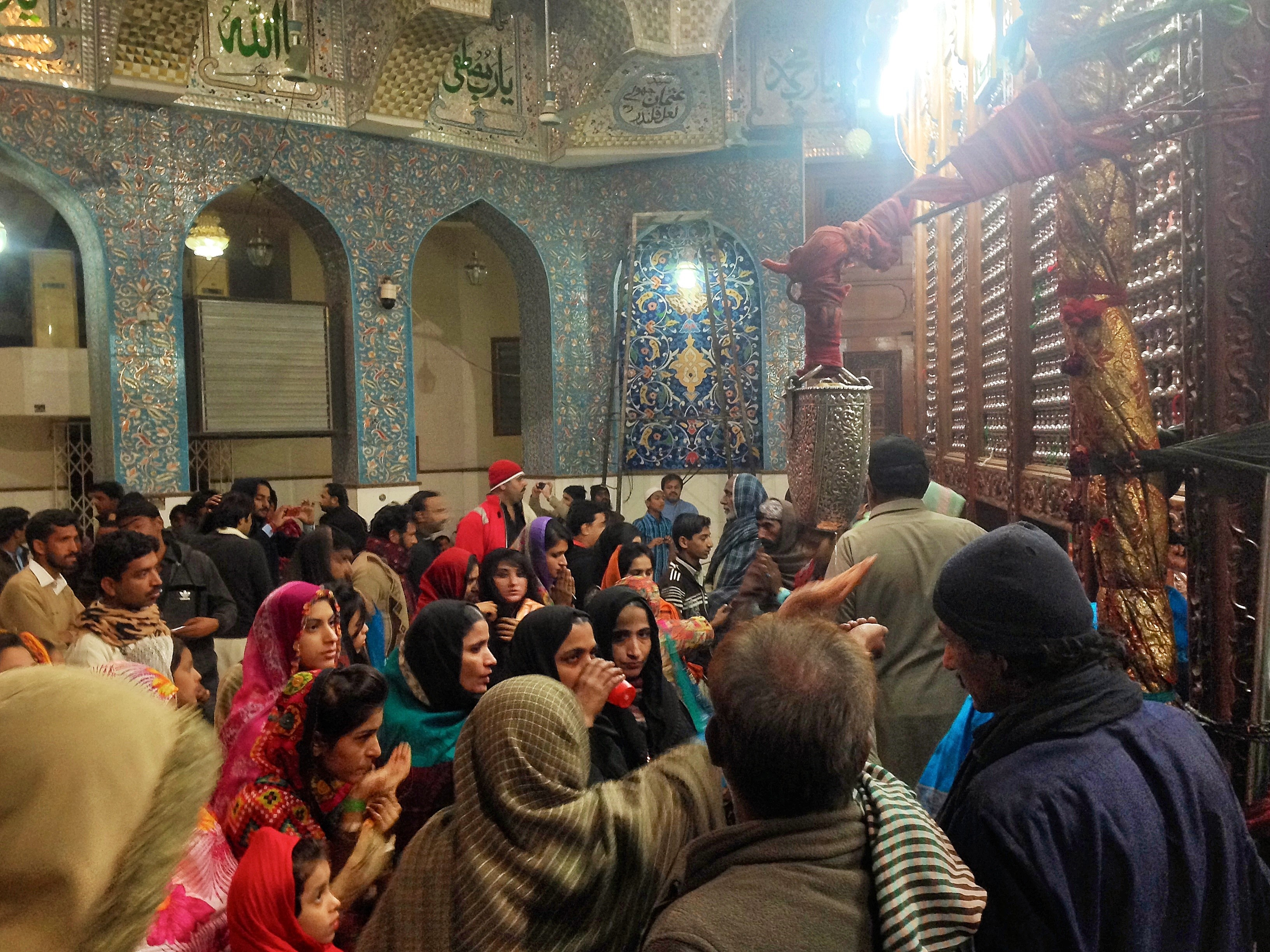Female worshippers reach for the rose water dispenser, tied to the grave of Shahbaz Qalandar. A visit to the Shrine acts as a form of both bodily and spiritual cleansing.