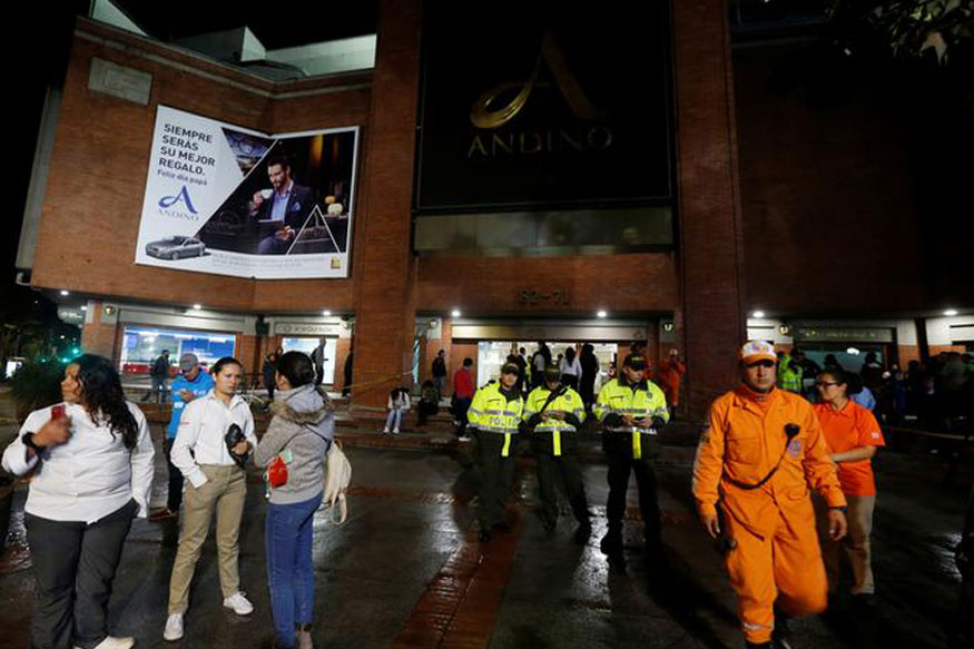 People, police officers and rescue personnel stand outside the Andino shopping center after an explosive device detonated in a restroom, in Bogota, Colombia (REUTERS)