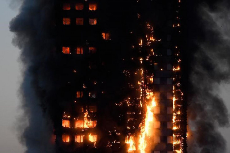 Flames and smoke billow as firefighters deal with a serious fire in a tower block at Latimer Road in West London
