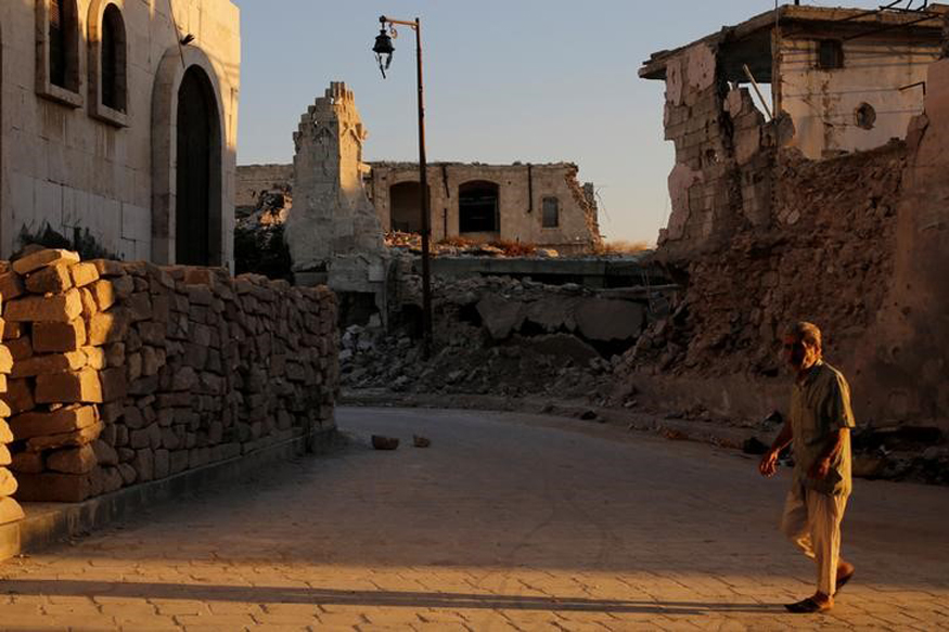 A man walks past damaged buildings in the old city of Aleppo
