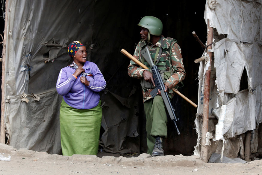 An anti riot policeman listens to a woman seeking refuge at a deserted makeshift stall during protests by supporters of opposition leader Raila Odinga, in Mathare, in Nairobi (REUTERS)