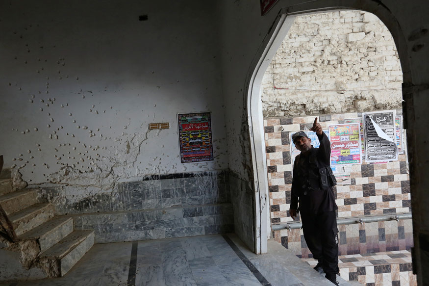A policeman gestures beside a wall with shrapnel-scars, which witnesses said was damaged in a suicide blast on January 2015, in a Shi'ite mosque in Shikarpur, Pakistan (REUTERS)