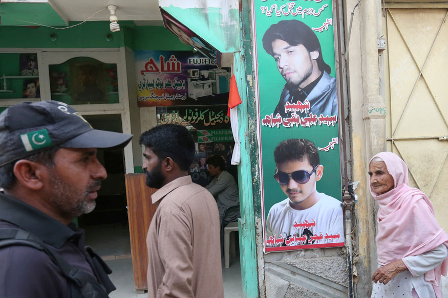 A policeman (L) and residents walk past a shop displaying the pictures of men, who were killed in a suicide blast on January 2015, in a Shi'ite mosque in Shikarpur, Pakistan (REUTERS)