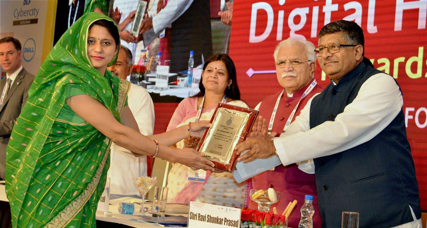 Gurugram: Union Minister for Electronics and Information Technology, Ravi Shankar Prasad and Haryana Chief Minister Manohar Lal giving away a award to a woman for rendering outstanding services in Atal Sewa Kendra at the Digital Haryana Summit-2017 in Gurugram on Friday. (Image: PTI)