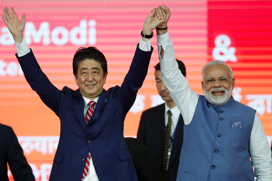 Japanese PM Shinzo Abe (L) and Prime Minister Narendra Modi raise hands after the groundbreaking ceremony for a high-speed rail project in Ahmedabad. (Photo: Reuters)