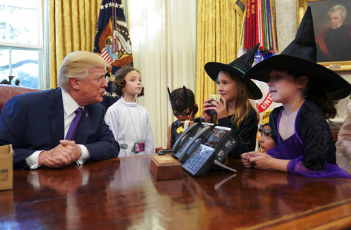 President Donald Trump talks to children dressed in Halloween costumes after handing out candy to them in the Oval Office of the White House, Friday, Oct. 27, 2017. The White House had invited the children of members of the media to visit the president and to trick-or-treat at the White House complex of the Eisenhower Executive Office building. Children from left are, Natalynn Parkson, 7, Yume Inone, 6, Phoebe Trabb, 7, Dylan Trabb, 3, and Ellie Thomas, 7. (AP Photo/Pablo Martinez Monsivais)