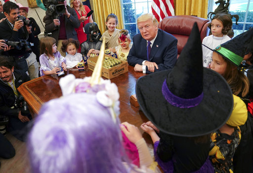 President Donald Trump meets with children dressed in their Halloween costumes in the Oval Office of the White House, Friday, Oct. 27, 2017. White House had invited the children of members of the media to visit the president and to trick-o-treat at the White House complex of the Eisenhower Executive Office building. (AP Photo/Pablo Martinez Monsivais)