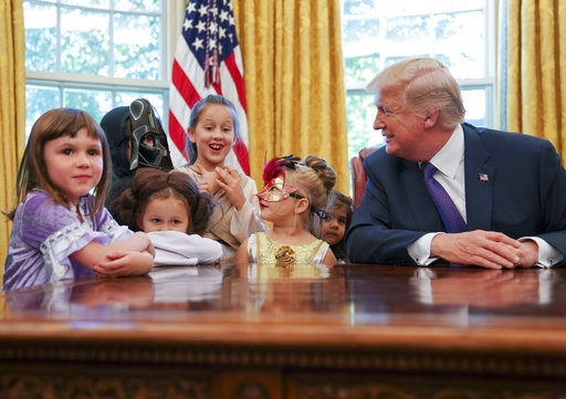 President Donald Trump meets with children dressed in their Halloween costumes in the Oval Office of the White House, Friday, Oct. 27, 2017. The White House invited the children of members of the media to visit the president and to trick-o-treat at the White House complex of the Eisenhower Executive Office building. (AP Photo/Pablo Martinez Monsivais)