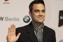 Robbie Williams performs with nude models