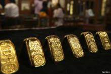 Gold falls to three-week lows on stronger dollar