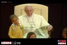 Boy wanders onto the stage during Pope' speech, clings to him, steals the show