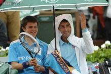 Novak Djokovic befriends a ball boy during a rain delay in his second round match of the French Open