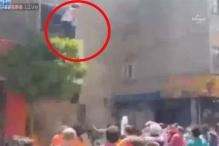 Watch: Heart-stopping moment a pregnant woman is caught on film jumping from a burning building into a waiting crowd