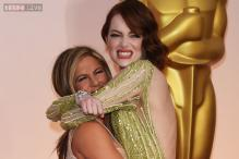 Photo of the day: Who minds a Versace gown? Jennifer Aniston lifts up Emma Stone at the Oscar's red carpet