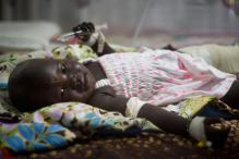 Thirteen-month-old baby in man's arms, the only two survivors of S Sudan plane crash