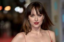 Look of the day: Dakota Johnson oozes oomph in a scarlet Dior gown on BAFTAs red carpet