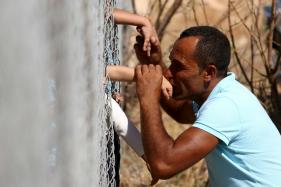 Apart For a Year, Syrian Family Shares Kisses Through Fence
