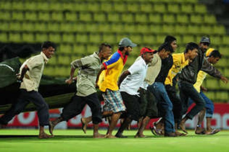 Sri Lankan ground staff are covering the pitch during the first T20 international between Sri Lanka and New Zealand at Pallekele Stadium. (Getty Images)