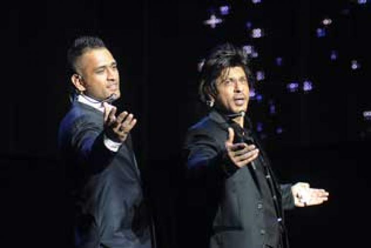 Chennai Super Kings captain MS Dhoni on stage imitating Shah Rukh Khan with the Badshah of Bollywood himself at the gala dinner held at the Emirates Palace Hotel in Abu Dhabi.