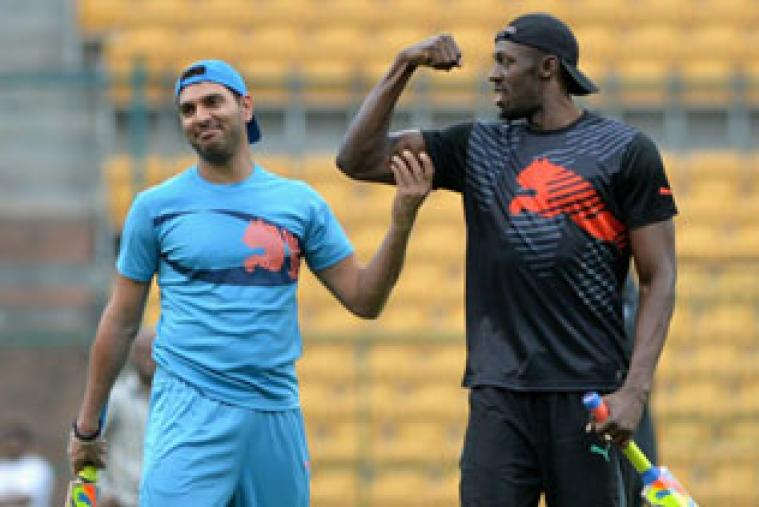 Jamaican Olympic Champion sprinter Usain Bolt flexes his biceps while Indian cricketer Yuvraj Singh looks on during a practice session prior to a four-over exhibition cricket match in Bangalore.