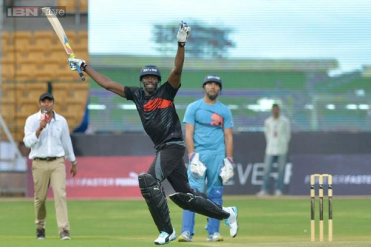 Usain Bolt celebrates after his team won the four-over exhibition match against Indian cricketer Yuvraj Singh's team at Chinnaswamy Stadium.