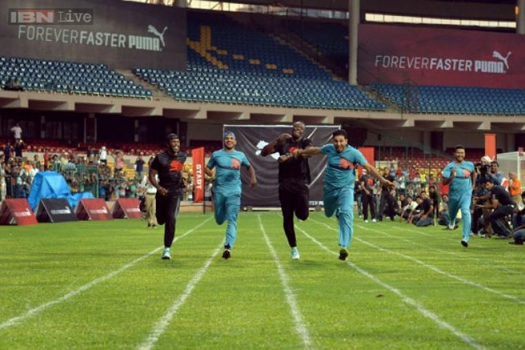 Usain Bolt and Yuvraj Singh tug each other as they take part in a 100 metre exhibition spint with fellow players after the match.
