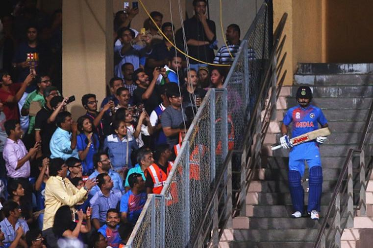 Fans at the Wankhede Stadium click pictures with their mobile phones as Virat Kolhi walks in to bat. (Getty Images)