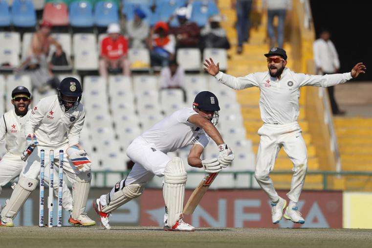 Indian cricketers celebrate as England's captain Alastair Cook, center, is bowled out by India's Ravichandran Ashwin on the third day of the Mohali Test. (AP Images)