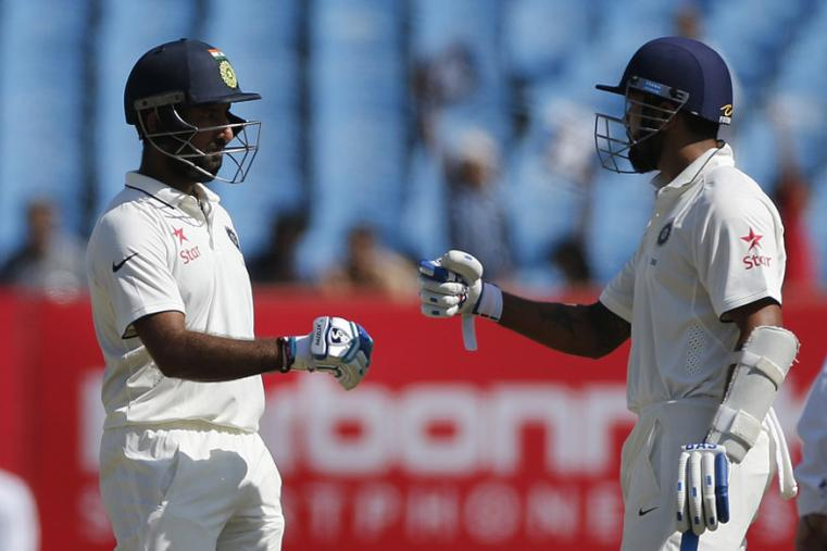 Indian batsman Cheteshwar Pujara is congratulated by team mate, Murali Vijay, as he completes a half-century on the third day of the Rajkot Test. (AP Images)
