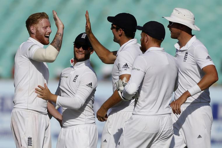 England's players celebrate after taking the wicket of Indian batsman Cheteshwar Pujara on the third day of the Rajkot Test. (AP Images)